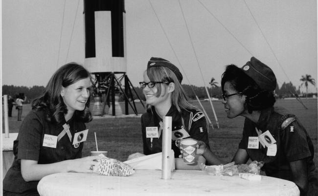 Three Girl Scout Seniors at Cape Kennedy sit at a table with a meal.